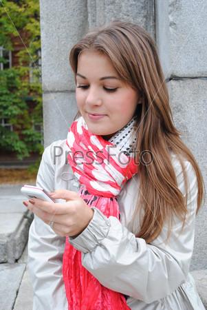 Молодая красивая девушка с мобильным телефоном