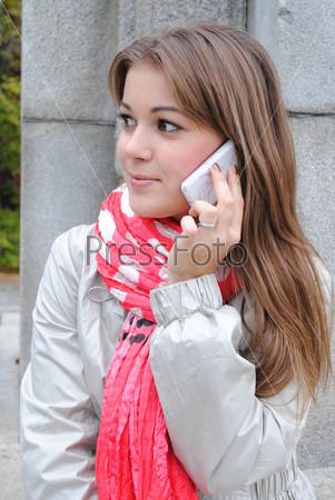Молодая красивая девушка говорит по мобильному телефону