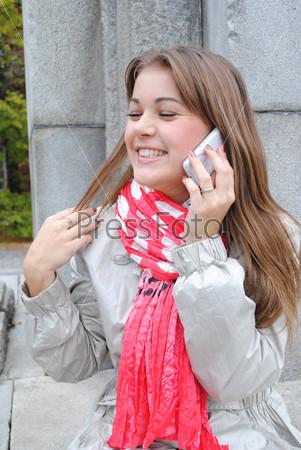 Счастливая девушка говорит по мобильному телефону