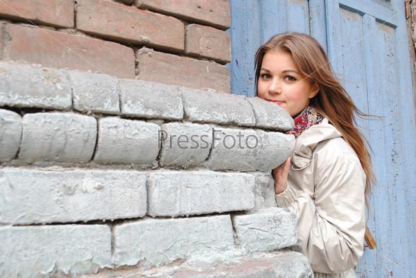 Фотография на тему Красивая девушка выглядывает из-за кирпичной стены на улице