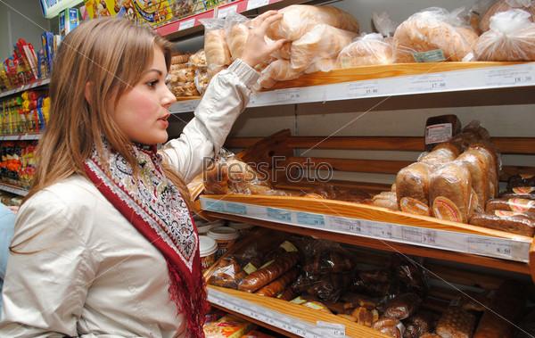 Фотография на тему Девушка выбирает хлеб в супермаркете