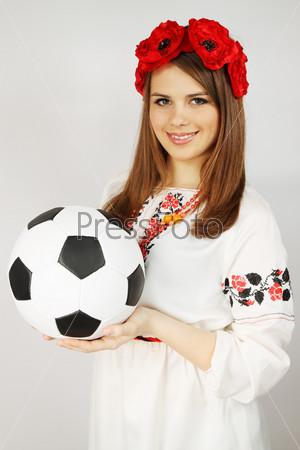 Фотография на тему Молодая женщина в украинском костюме держит мяч