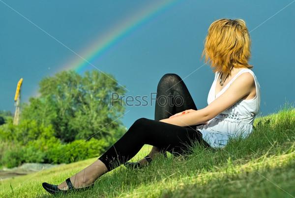 Молодая красивая женщина на фоне неба с радугой