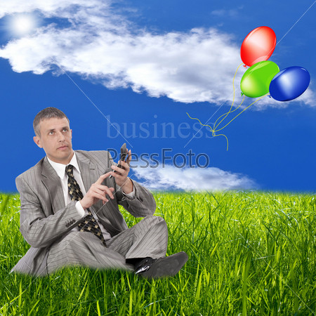 Бизнесмен сидит на зеленой траве и считает на калькуляторе прибыль