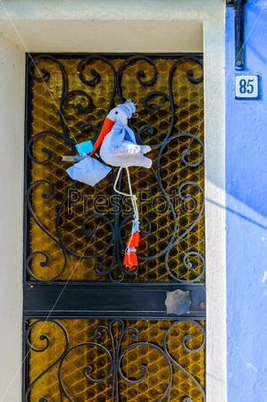 Дверь с аистом на одном из красочных домов в Бурано, Венеция, Италия