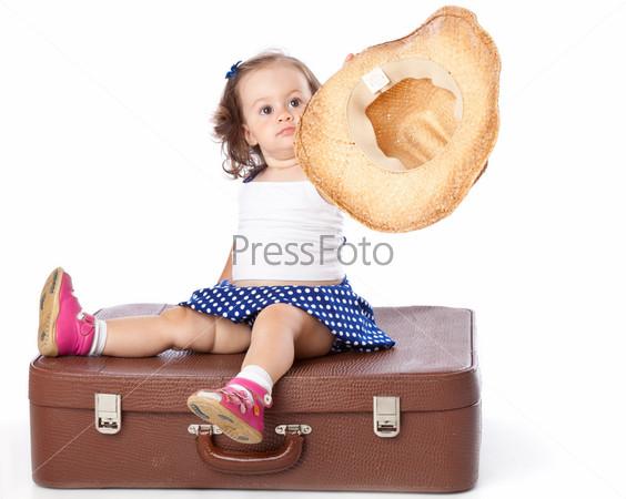 Смешная девочка сидит на чемодане, изолированная на белом фоне
