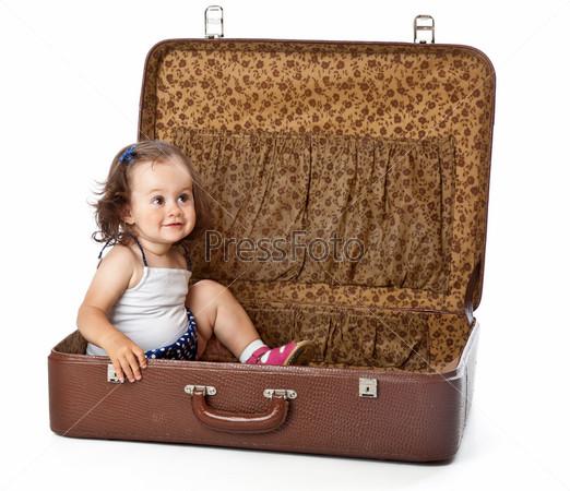 Фотография на тему Смешная девочка сидит в чемодане, изолированная на белом фоне