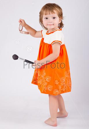 Симпатичная девочка собирается нанести макияж. Серый фон