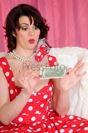 Удивленная женщина с долларом. одетая в стиле пин-ап
