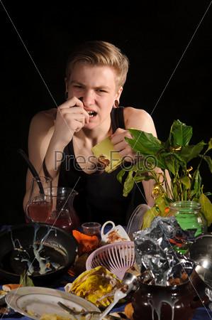 Молодой человек с чашкой сидит за грязным столом