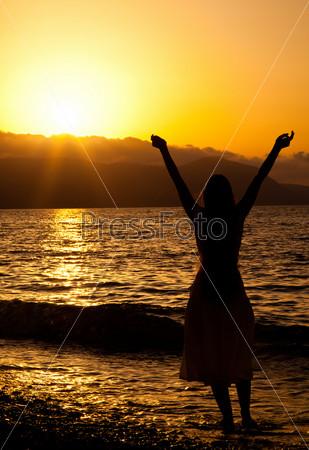 Фотография на тему Стройная девушка наслаждается свободой, глядя на закат над морем
