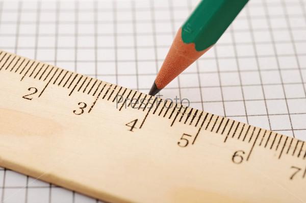 Фотография на тему Деревянная линейка и карандаш на фоне клетки крупным планом