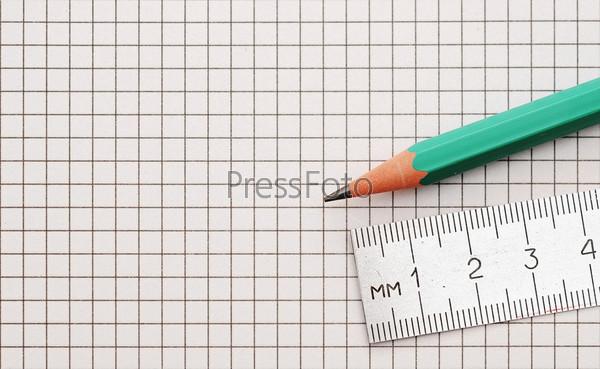 Стальная линейка и карандаш на фоне клетки крупным планом