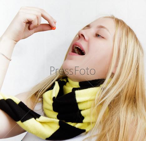 Девушка с таблетками, завернутая в шарф, на белом фоне