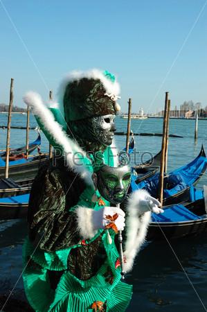 Фотография на тему Человек в зеленой маске на набережной канала Сан Марко в Венеции во время карнавала в 2011 году, Италия