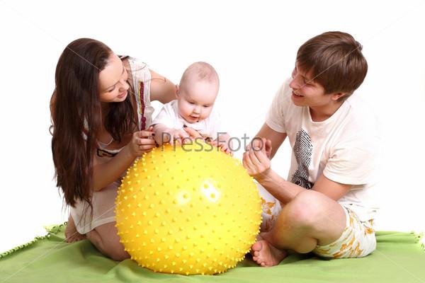 Портрет молодой семьи на зеленом покрывале. Папа, мама и малыш