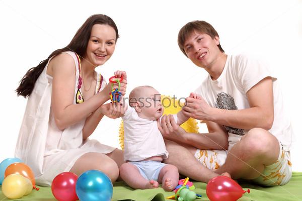 Фотография на тему Портрет молодой семьи. Папа, мама и малыш играют в игрушки на зеленом покрывале