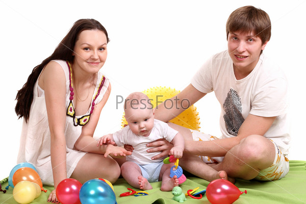 Портрет молодой семьи. Папа, мама и малыш играют в игрушки на зеленом покрывале