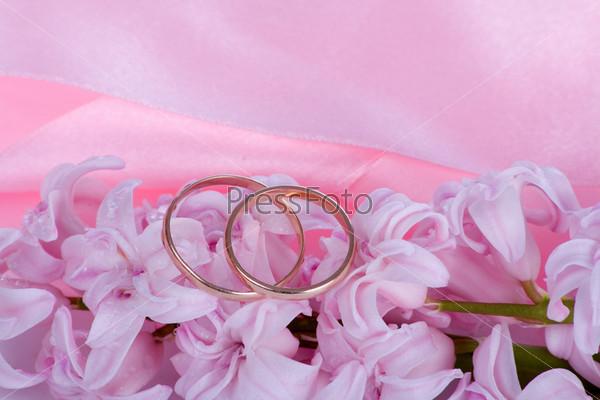 Два обручальных кольца на розовом фоне с гиацинтами