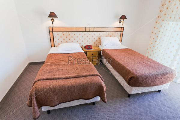 Две простые дешевые кровати в гостиничном номере
