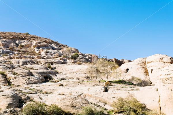 Гробницы и жилища на склоне горы на пути в город Петра, Иордания