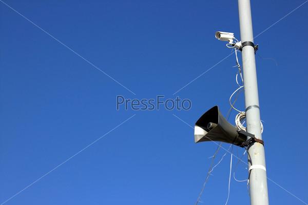 Видеокамера и громкоговоритель на столбе на фоне голубого неба