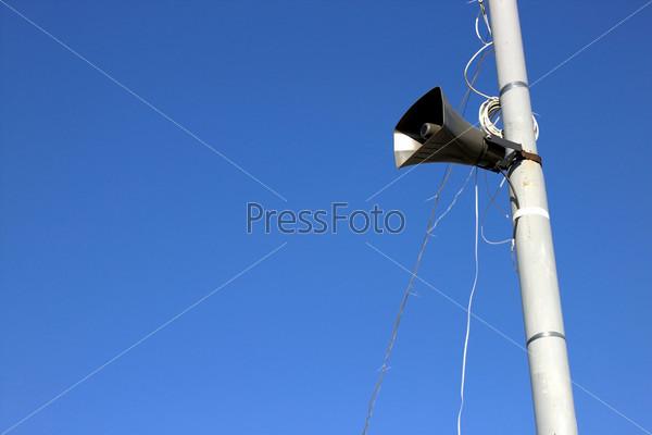 Громкоговоритель на столбе на фоне голубого неба