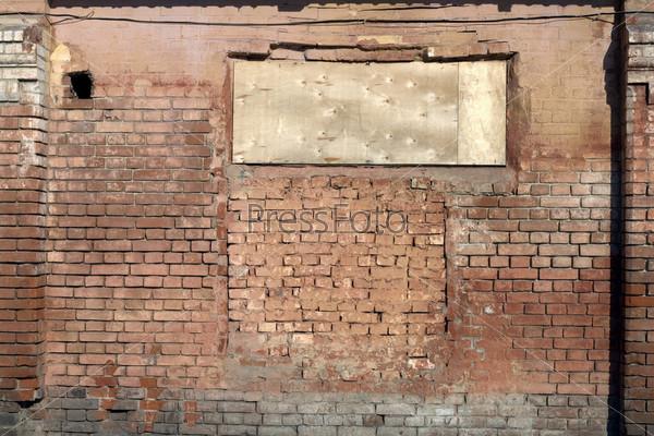 Заколоченное окно на древней кирпичной стене
