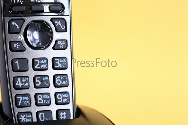 Современный черный беспроводной телефон на желтом фоне с пространством для текста