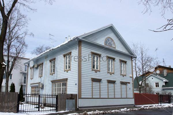 Двухэтажный деревянный дом на тихой улице на окраине города