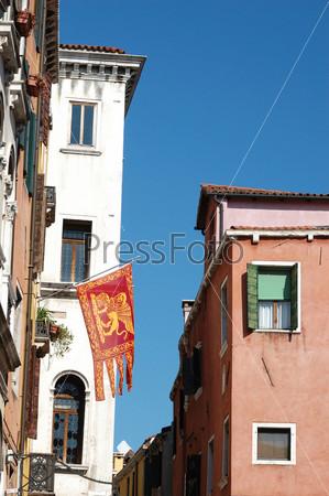 Старинные дома и венецианский флаг со львом Святого Марка, Италия