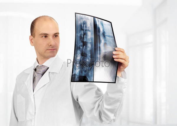 Молодой привлекательной врач изучает рентгеновский снимок
