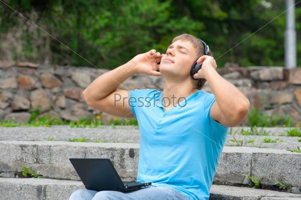 Молодой человек с ноутбуком слушает музыку на улице