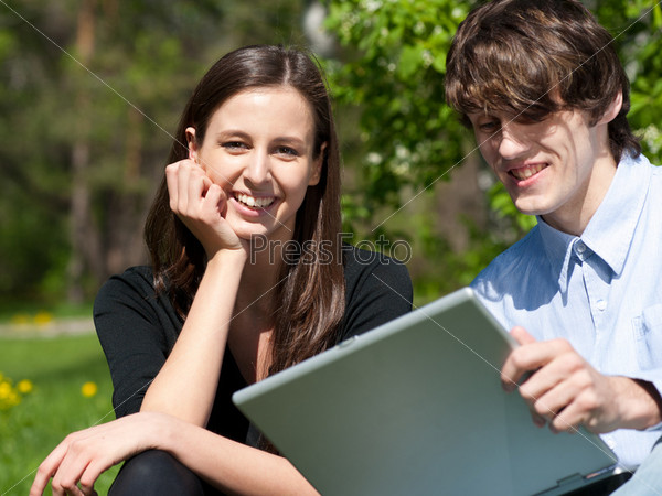 Фотография на тему Молодая счастливая пара использует лэптоп на улице