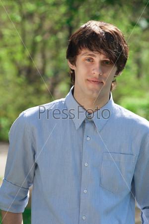 Красивый молодой человек в повседневной одежде на прогулке в парке