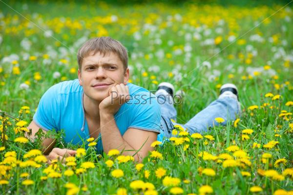Красивый молодой человек лежит на траве и улыбается