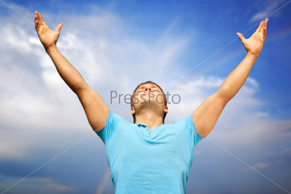 Счастливый молодой человек с поднятыми руками и закрытыми глазами на фоне голубого неба