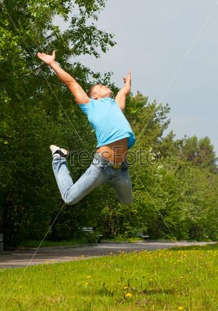 Фотография на тему Счастливый молодой человек прыгает в воздухе с распростертыми руками на свежем воздухе