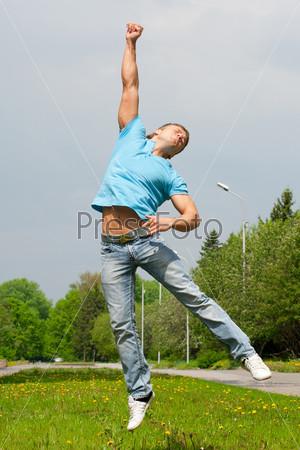 Счастливый молодой человек прыгает с поднятой рукой на свежем воздухе