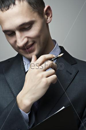 Портрет улыбающегося бизнесмена с ручкой и документами
