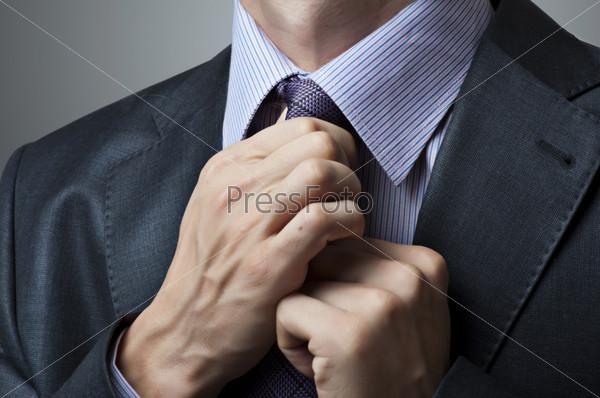 Деловой человек поправляет галстук
