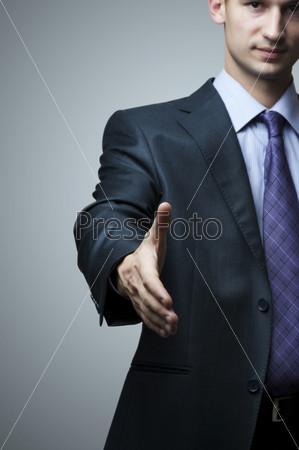 Деловой человек протягивает руку для приветствия