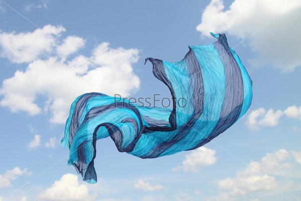 Летящий шелковый платок на фоне голубого неба