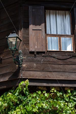 Фрагмент старого деревянного дома. Окно и старый фонарь. Несебр, Болгария