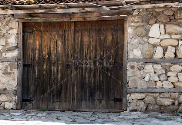 Старые деревянные ворота в каменной стене