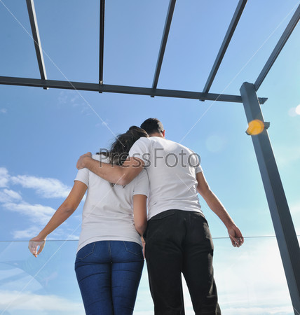 Счастливая молодая пара на балконе на фоне неба.