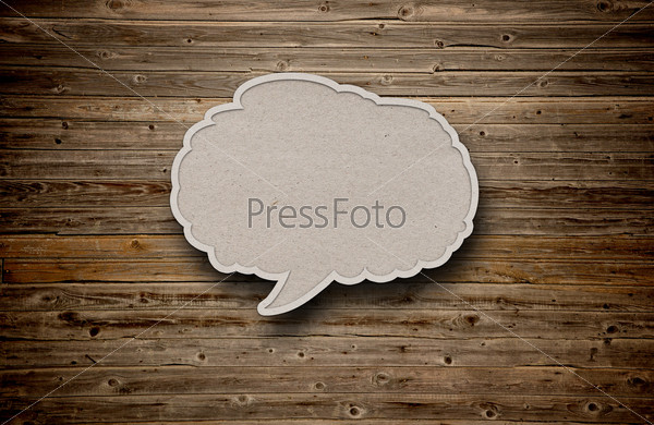 blank recycled paper speech bubble on wood background