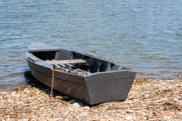 The wooden boat on the river bank