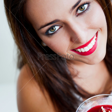 Portrait of an young beautiful woman eating an ice cream in cafe