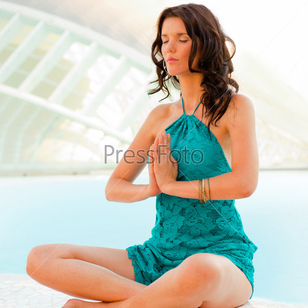Portrait of pretty young woman doing yoga exercise on ground at